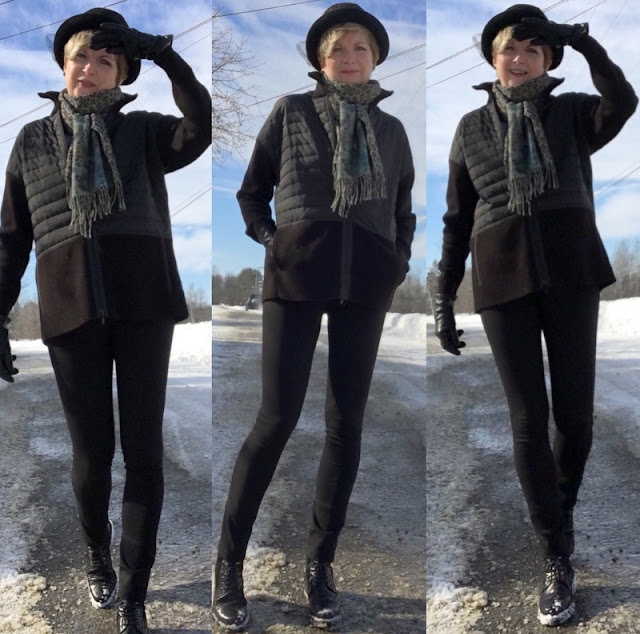 woman in black pants and jacket and a bowler hat, outside on a sunny winter day
