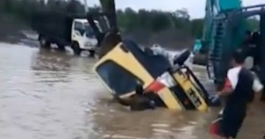 Dramatic moment digger driver saves trucker's life on flooded Indonesian road