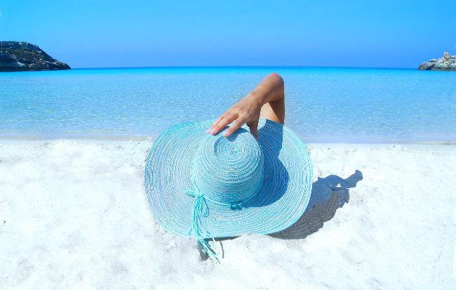 Donna con cappello di paglia sulla spiaggia sotto il sole