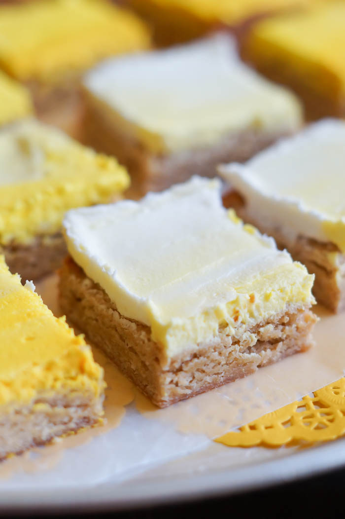 Frosted Lemon Cookie Bars with a sunshine-y ombre yellow frosting.   bakeat350.net