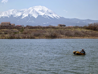 Wahatoya Lake Reservoir with a fisherman in a float tube. Mountains in background.