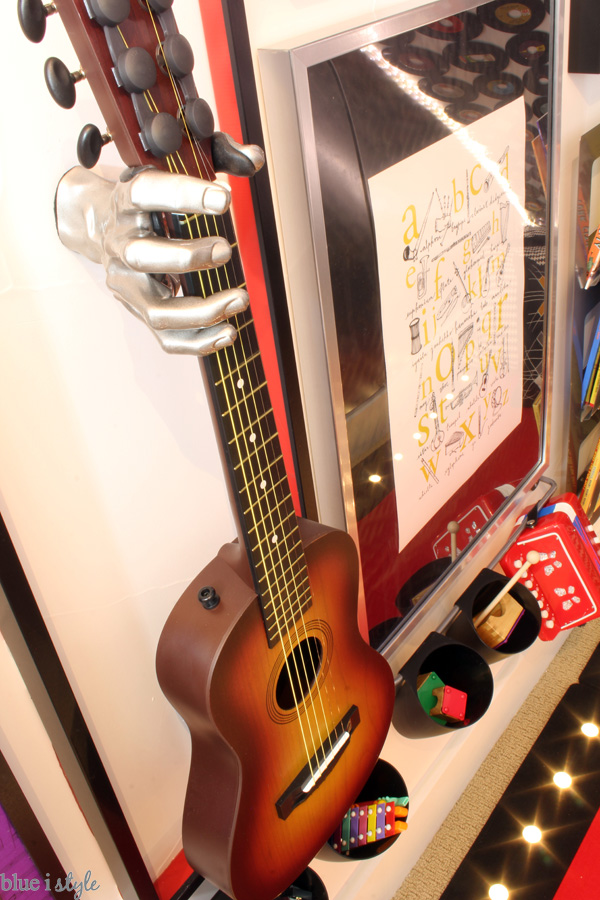 Hand holding guitar in under stair playroom