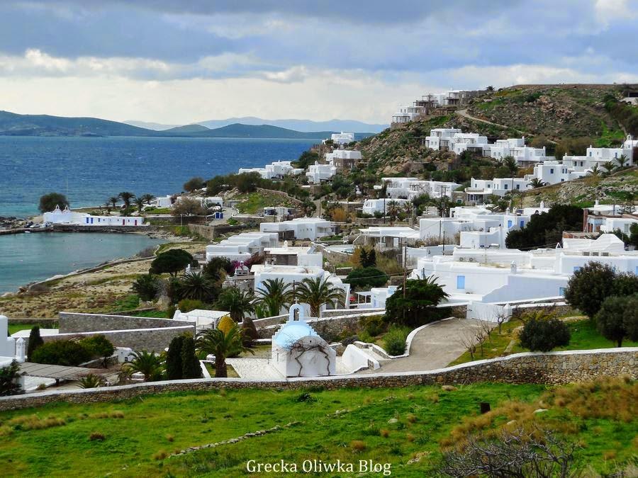 Mykonos Grecja, białe kubistyczne domki na tle niebieskości i zieleni