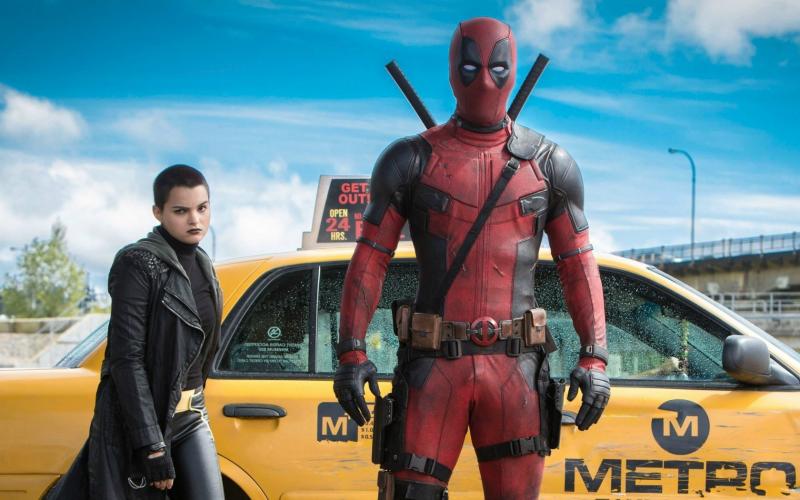 Na imagem, Deadpool olha diretamente pra câmera enquanto uma garota de cabelos curtos e casaco preto de couro fecha a porta do táxi no qual eles vieram.