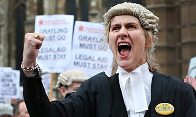 Photo of angry Barristers protesting the 2012 changes to legal aid funding and lack of representation. A female barrister in court dress, shouts her displeasure, wearing an I Heart Legal Aid badge. Court Complexities and Legal Fiction, A Moron In A Hurry marchmatron.com