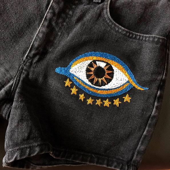 Embroidered eye with stars handstitched onto a pair of black denim shorts