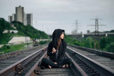 Chica con sudadera y capucha sentada en las vías del tren