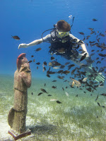 fish surround diver as he looks at underwater statues on first dive