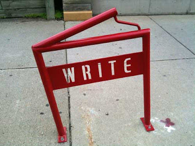 Red metal bike rack shaped like an open book with the word WRITE in open stencil letters