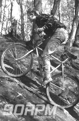 Un uomo pedala su una salita nel bosco in sella ad una bicicletta mountain bike.