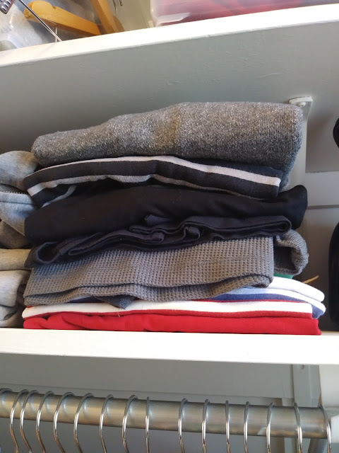a neatly folded stock of long-sleeved shirts