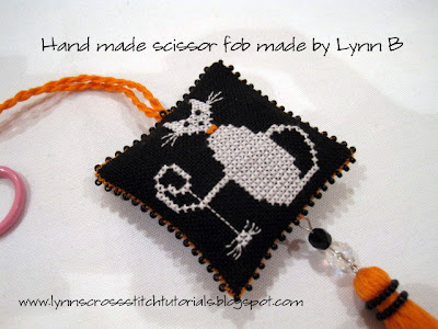 Halloween cross stitched scissor fob tutorial showing black beaded scissor fob with ghost cat embroidered  in cross stitch