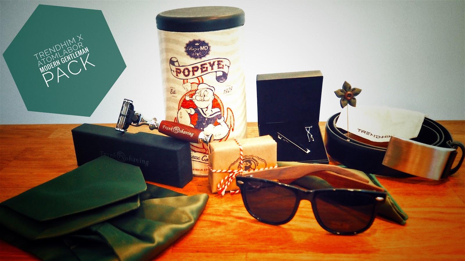Männerpflegeprodukte auf einer Holztheke vor weißem Hintergrund - Rasierer, Sonnenbrille, Accesoires, Bartseife,