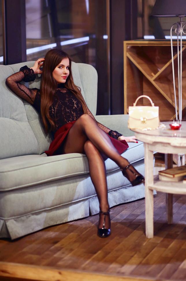 Czarna koronkowa bluzka, bordowa spódniczka, rajstopy ze szwem i lakierowane buty