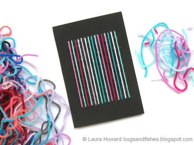 Notecard decorated with yarn stripes