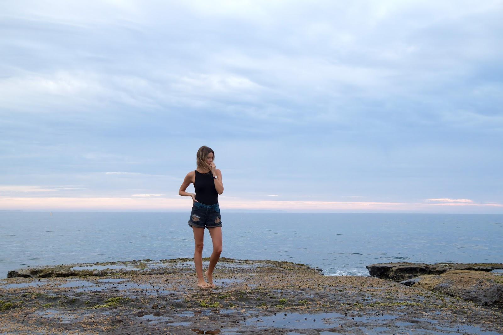 Fashion and travel blogger, Alison Hutchinson, with the sunrise at Mollymook Beach in Australia