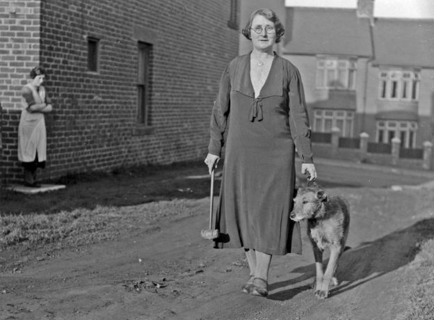 Knocker up Mrs Bowers of Greenfield Terrace walking with her dog carrying her knocker up mallet. Knocker Up. marchmatron.com