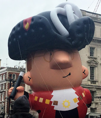 Pic of giant balloon of giant mayor in regalia held down with strings