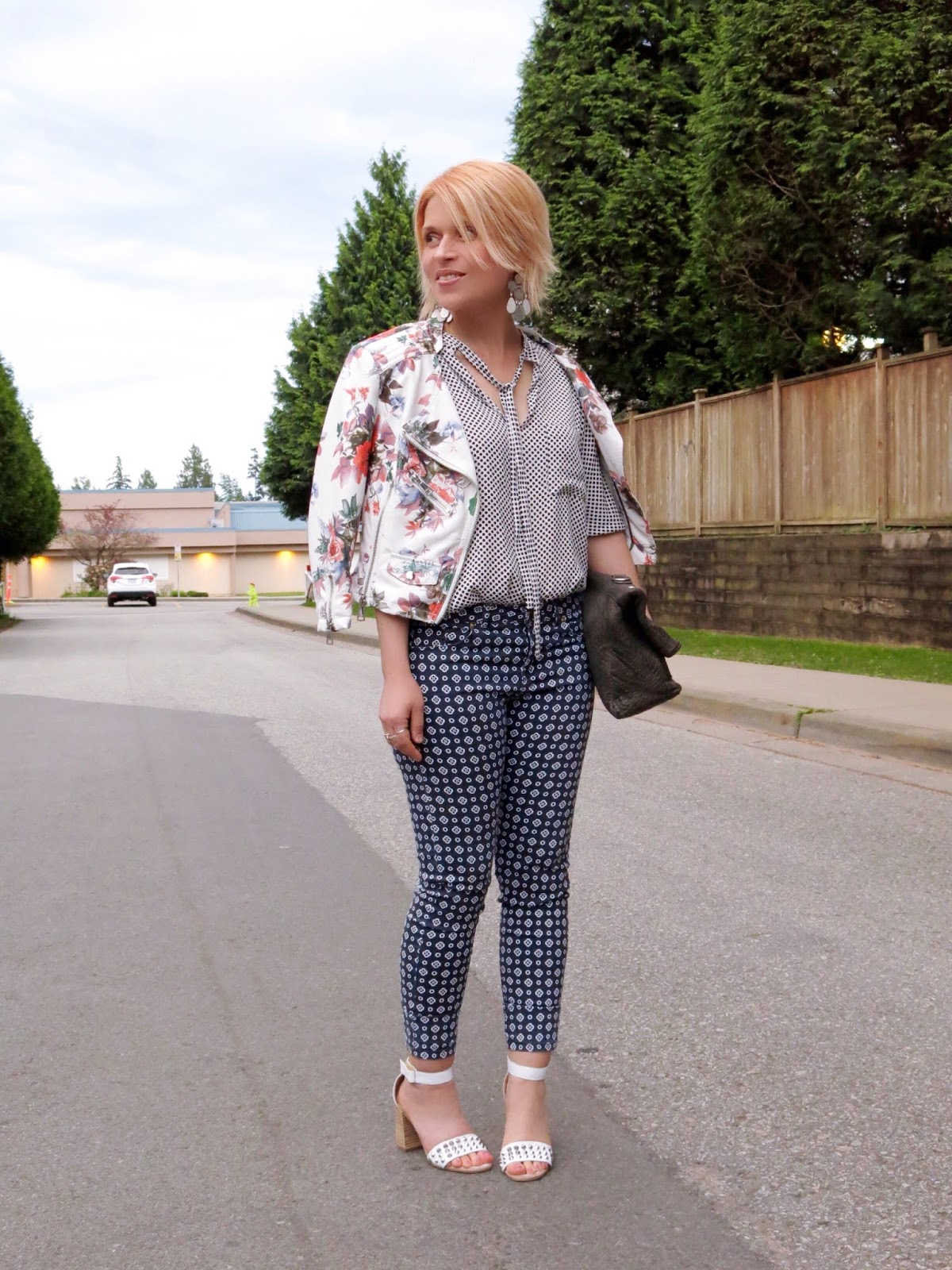 styling patterned jeans and a dotted blouse with a floral moto jacket and white ankle-strap sandals