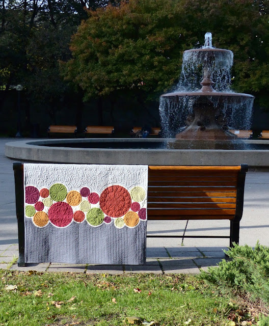 Another photo of Bubbles for Malcolm quilt on a bench by a fountain