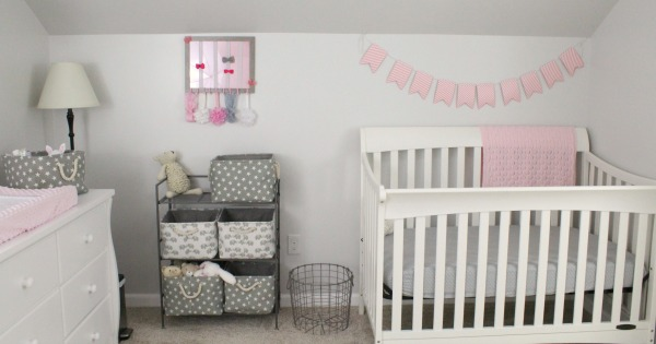 Gray white and light pink nursery for a baby girl- Minky pink changing pad cover, white dresser as changing table, grey canvas and rope decorative storage baskets, metal wire laundry basket, white crib from Target with polka dot fitted sheet and pink flag banner decoration