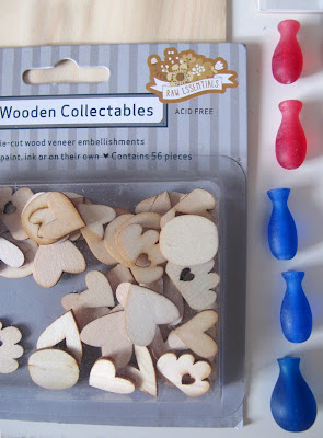 A packet of wooden cutouts in the shape of hearts and clouds and five plastic vase-shaped pieces.