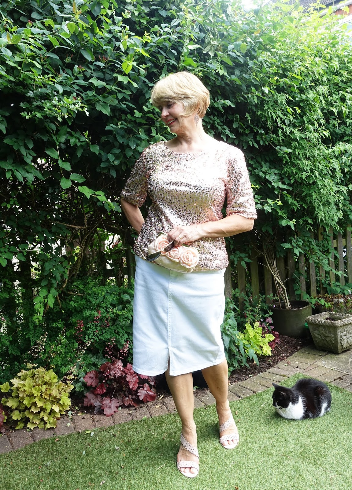 Woman in a rose gold sequin top and white pencil skirt