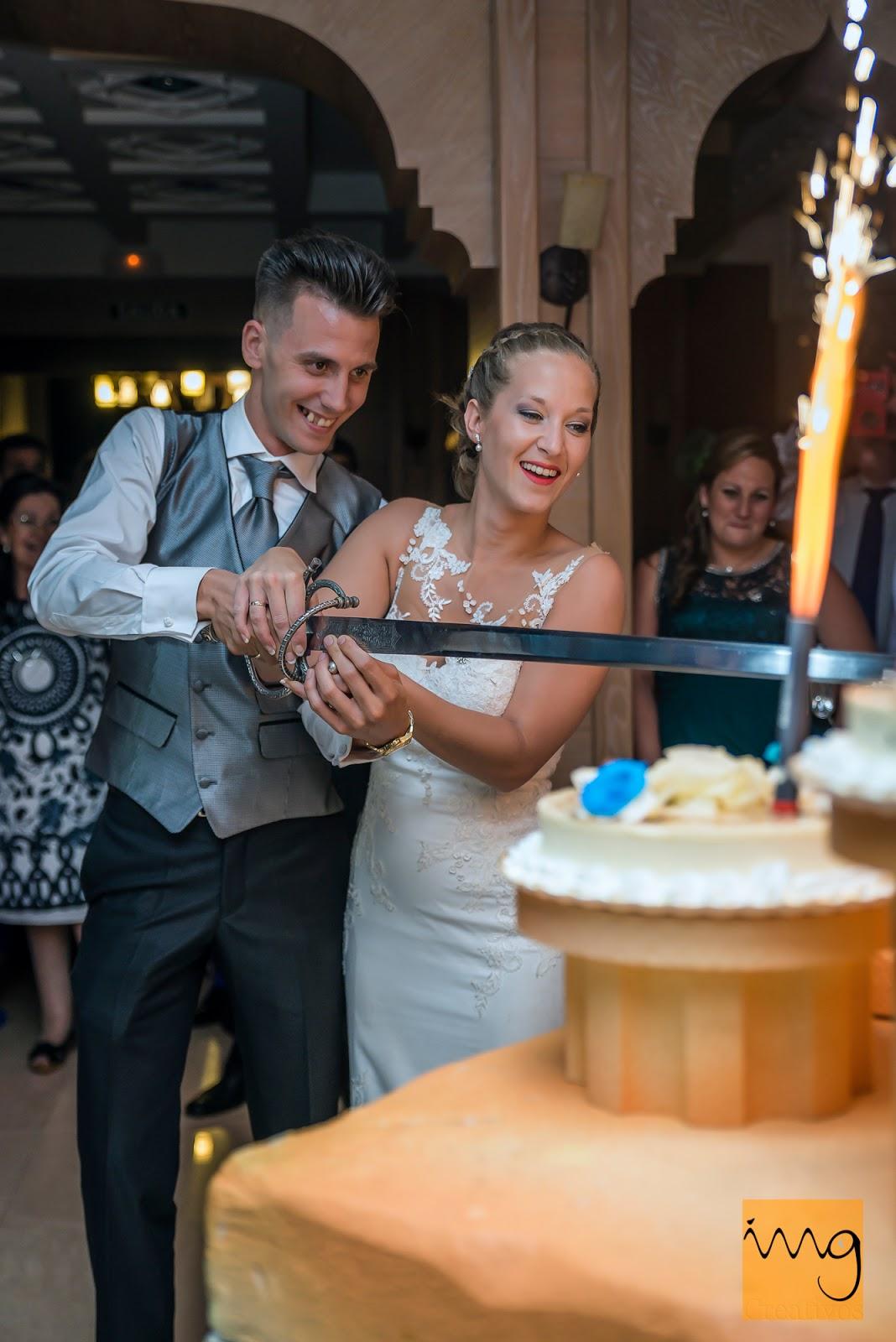 Fotografía de los novios haciendo el honor de cortar la tarta de boda