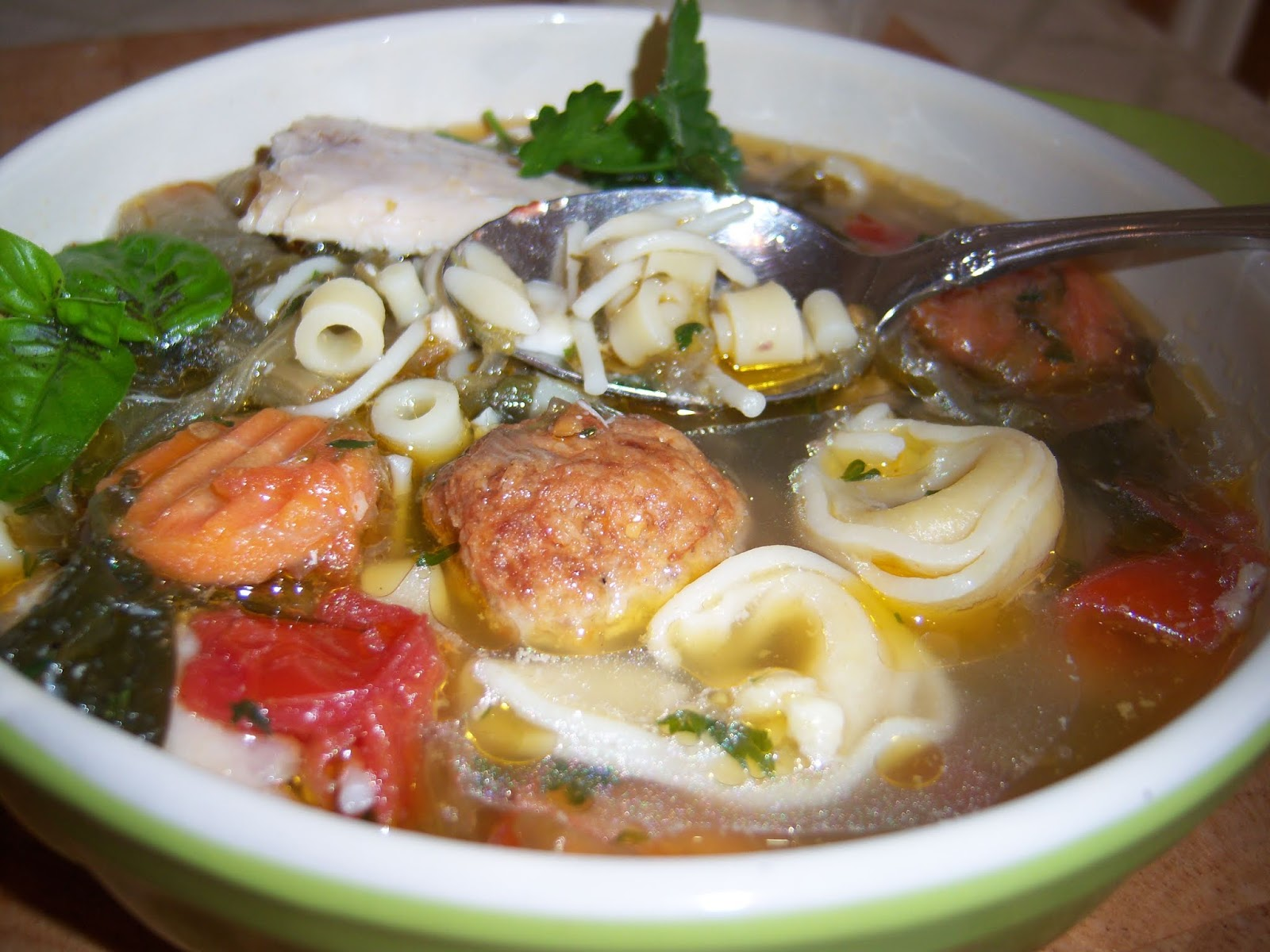 this is a white bowl of Italian Wedding  Style Tortellini  Soup. The soup has various kinds of pasta like ditalini, tortellini in a chicken broth with pastine, escarole, carrots with tomatoes and fresh herbs.