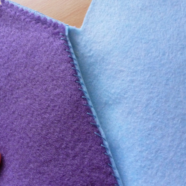 Whip stitch on blue and purple felt fabric
