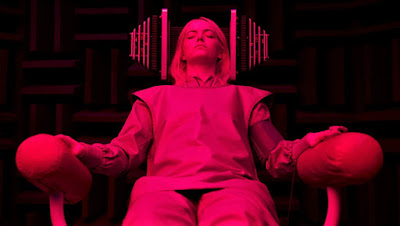 Young woman in institutional clothing with eyes closed, in a chair with futuristic machinery on both sides of her head