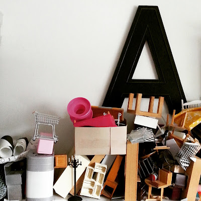 Shelf full of various pieces of 1/12 dolls' house furniture, stacked up in a higgledy-piggledy pile.