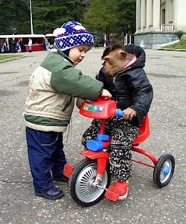 child helping monkey to ride a tricycle