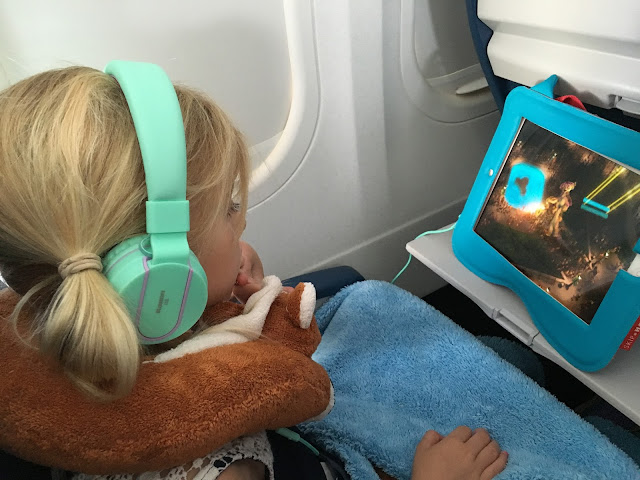 Little girl watching movie on Ipad on a plane