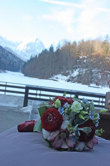Winterbrautstrauß von Passiflori mit Baumwolle. Winterhochzeit in den Bergen am Riessersee Hotel Garmisch-Partenkirchen in Bayern, Kupfer, Dunkelrot, Hellblau, Grau, Winter wedding abroad Bavaria in copper, ruby red, light blue