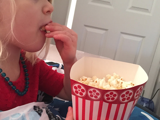 A young girl eating popcorn out of a cardboard box
