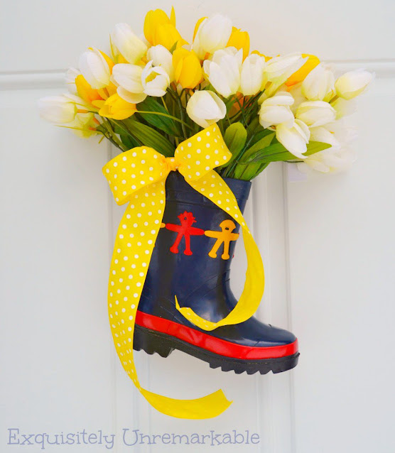 Small rubber rain boot on front door with tulips and yellow bow