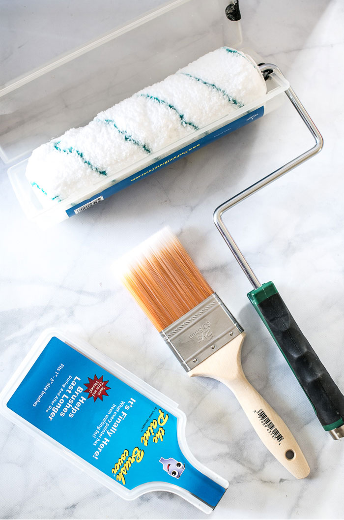 Paint brushes and roller in plastic covers