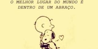 Em um retângulo amarelo claro, ao centro, Charlie Brown e seu cãozinho Snoopy, abraçados e próximo a eles solto no ar, um pequeno coração! No topo, em letras pretas maiúsculas, lê-se: O melhor lugar do mundo é dentro de um abraço. Taí o recado a todos: Um Feliz Dia do Abraço!