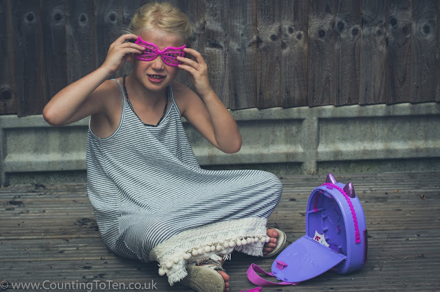 A young girl trying on the toys sunglasses, sitting next to the open hard plastic purple backpack