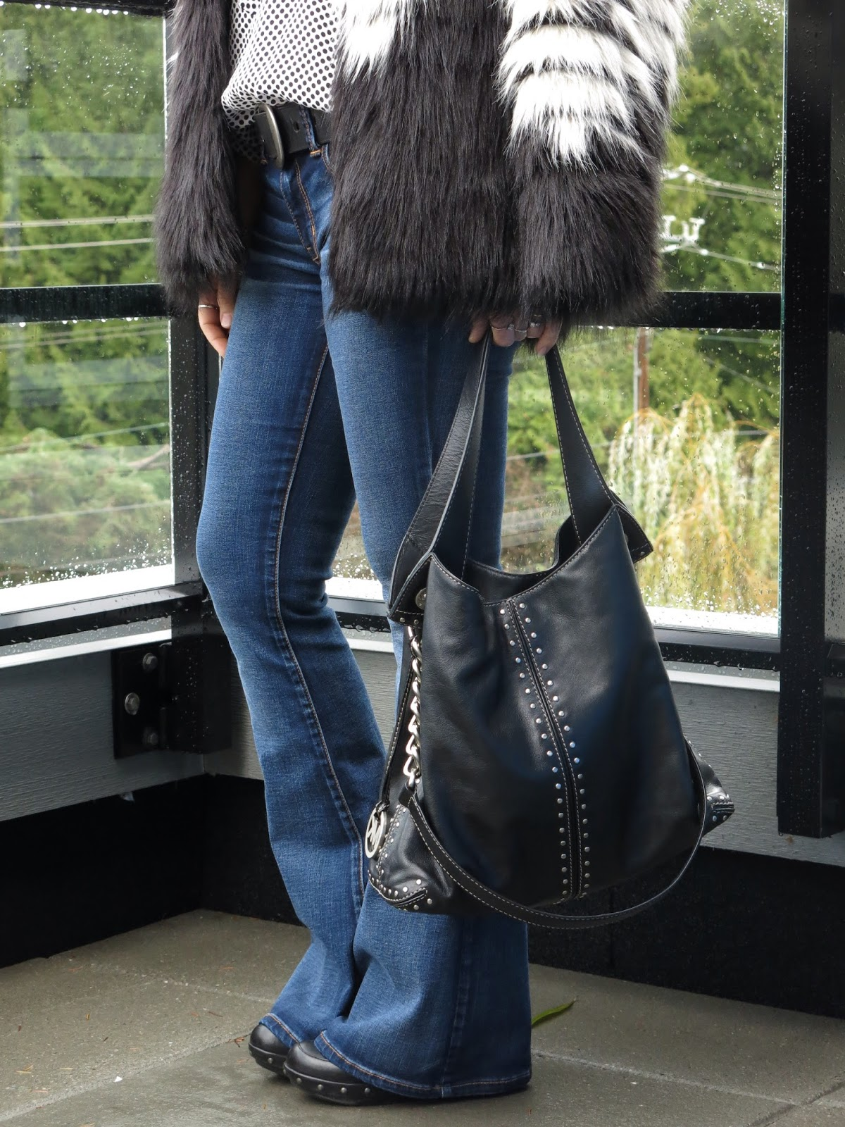 colour-blocked faux-fur jacket, polka-dotted blouse, flare jeans, and Michael Kors bag