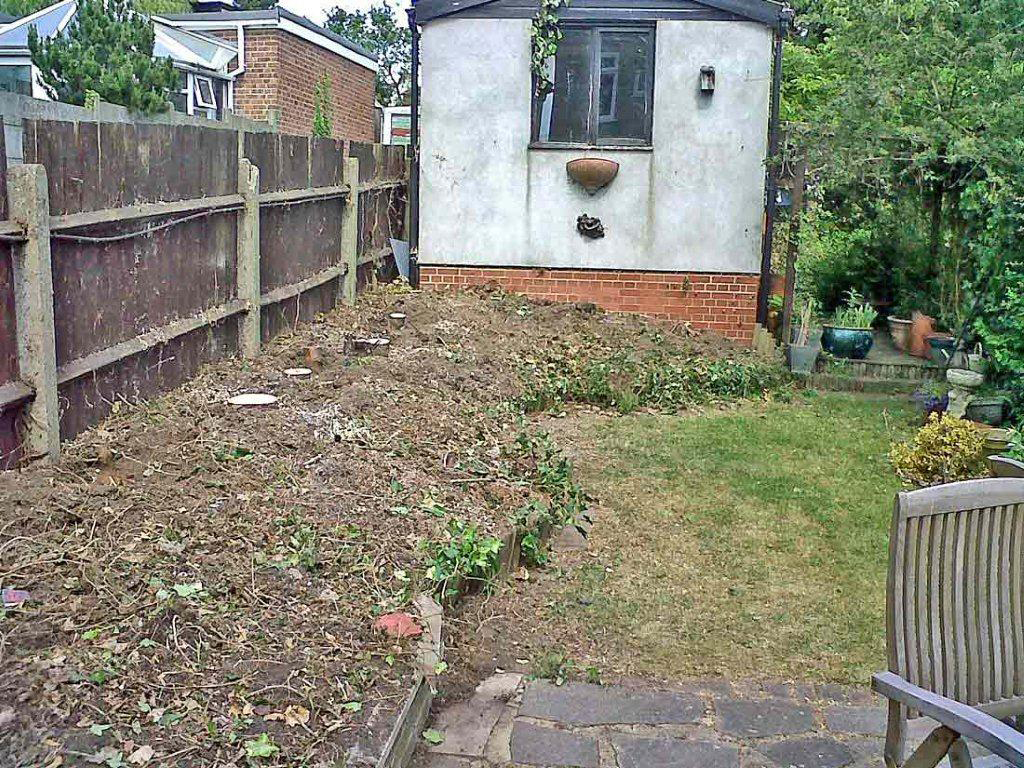 Image showing a small London back garden before its makeover. The border is full of dry poor quality soil after Leylandii trees have been removed and the grass is in bad condition.
