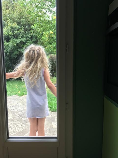une adorable petite fille a abandonné son manteau rouge pour sortir dans le jardin