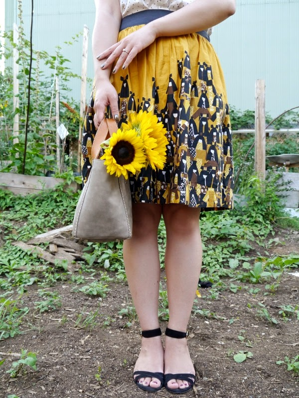 Yellow and black patterned full skirt, sunflowers, grey tote, black ankle strap sandals