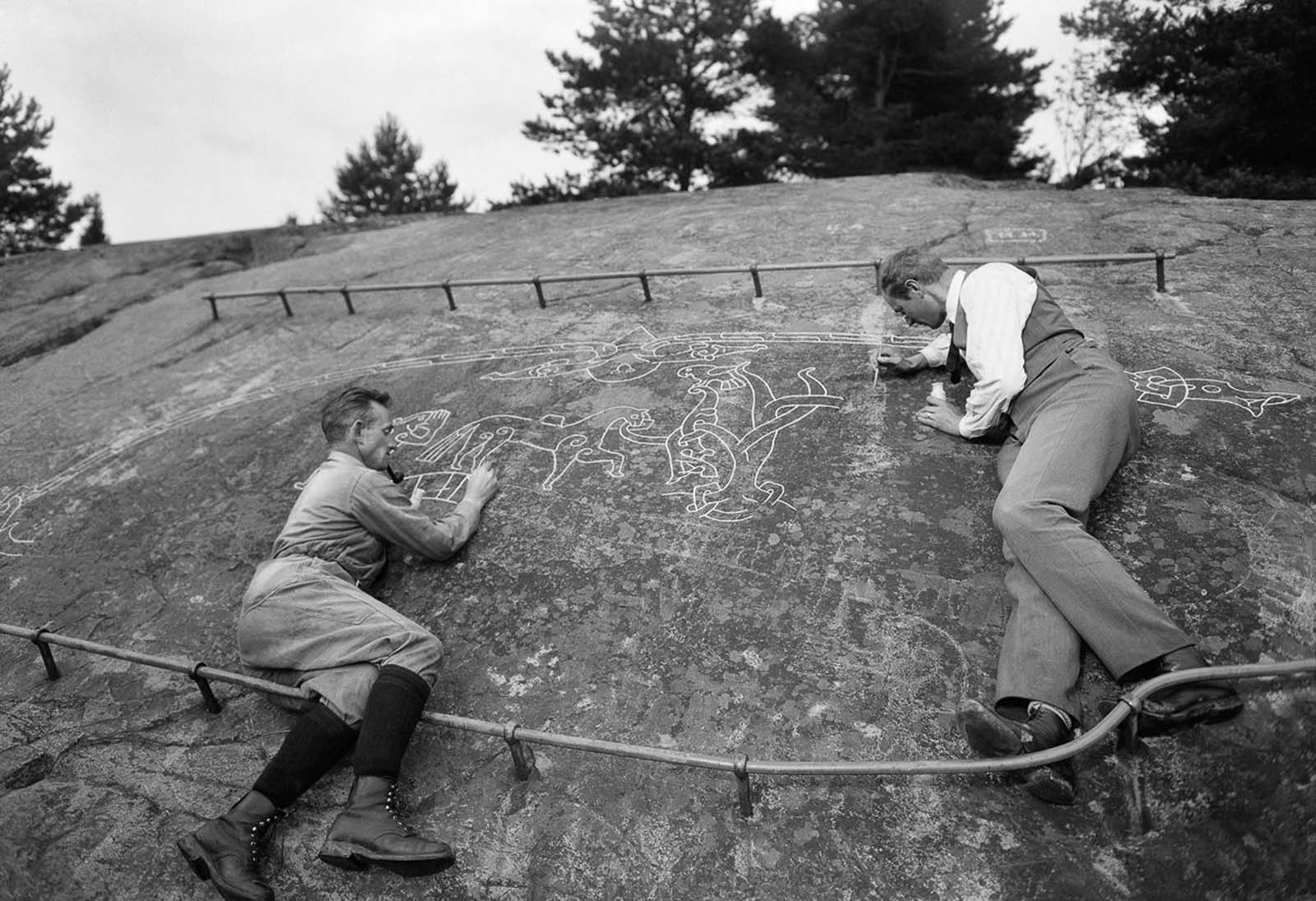 Harald Faith-Ell and Elias Wessén paint in the runes of the Sigurd carving on the Ramsund rock. The Viking Age carving depicts the Old Norse Sigurd saga, about the hero Sigurd who killed the dragon Fafner. The inscription reads,