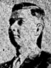 Headshot from news clipping showing middle-aged white man with brown or dark-blond hair parted on the left