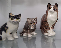 Three cat figurines in a case at the American Museum of the House Cat.