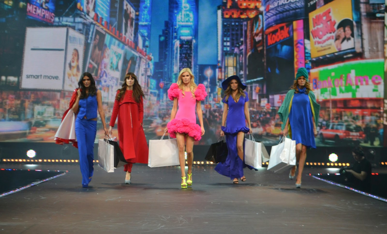 5 models walking down the runway. an image of times square is being used as a backdrop