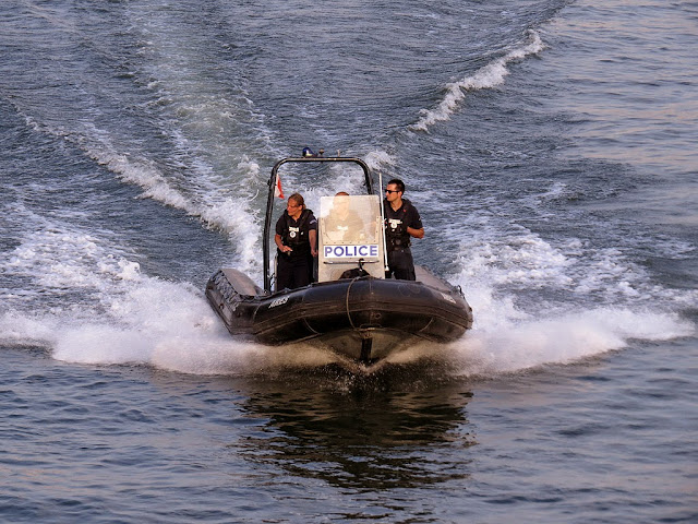 Police patrolling the Seine on a fast boat, seen from the Pont des Arts, Paris