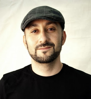 Head shot of poet Craig Santos Perez in a cap
